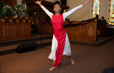 young black woman dancing in a red and white outfit