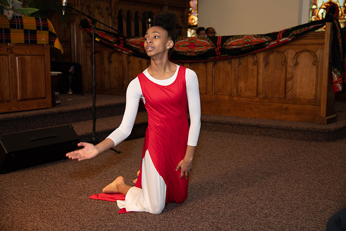 young woman in red dancing during church service