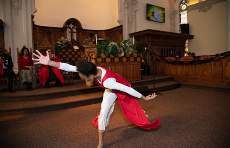 young woman in red dancing in front of church