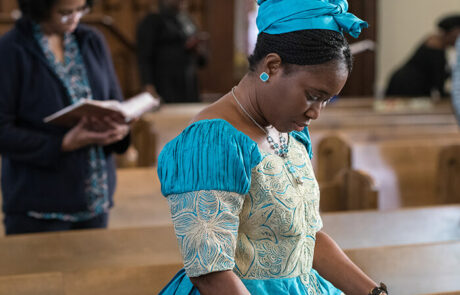 young black woman in bright blue dress praying