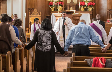 church members holding hands and praying
