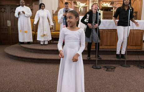 young black child singing with adults during church service