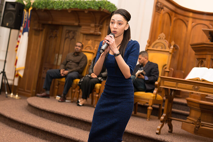 young woman in blue dress singing during church service
