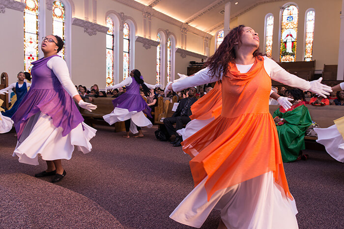 young women dancing in colorful outfits during church service
