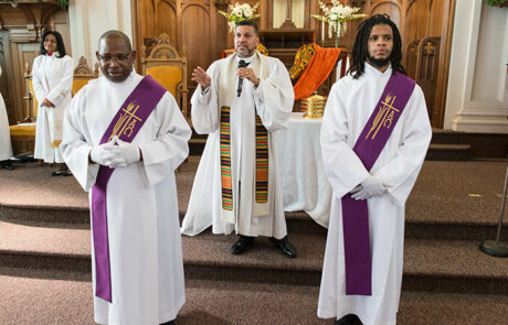 men in white robes with purple accents during a church service