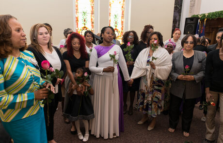 congregation members holding pink roses