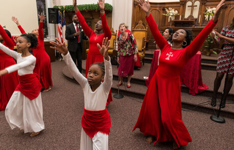 group of women of all ages wearing red and dancing during a church service