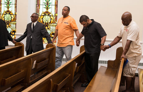 group of men holding hands and praying