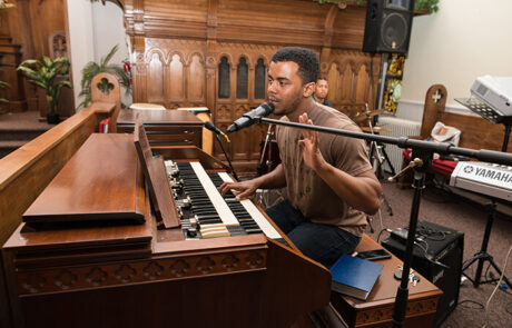 young black man singing and playing piano in church