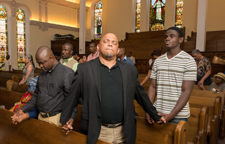young men holding hands together while standing in pews