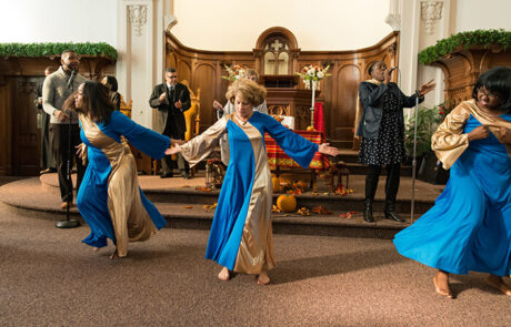 group of dancers in flowy gold and blue outfits with singers behind them at a church service